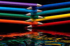 Colored pencils on black background reflected in water. Stock Photos