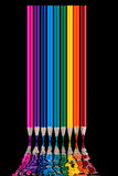 Colored pencils on black background reflected in water. Royalty Free Stock Photo