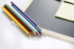 Colored pencils and black board. Isolated on white background Royalty Free Stock Photos