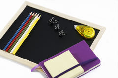Colored pencils, black board, notebook and memopad. Back to school, back to work Royalty Free Stock Photo