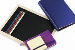 Colored pencils, black board, notebooks and memopad. Back to school, back to work Stock Image