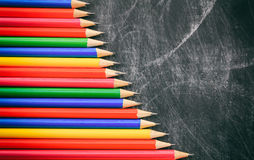 Colored pencils on a black board. Colored wooden pencils on a black chalkboard Stock Photography