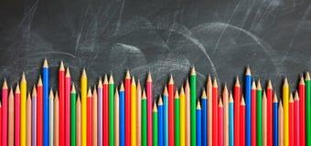 Colored pencils on a black board. Colored wooden pencils on a black chalkboard stock images