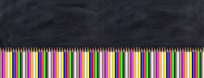 Colored pencils on a blackboard. 3d illustration. School concept - Colored pencils on a black chalkboard. 3d illustration Royalty Free Stock Image
