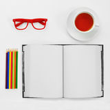 Colored pencils, blank notebook, eyeglasses and cup of tea on a. High-angle shot of a some colored pencils, a blank notebook, a pair of red plastic-rimmed Royalty Free Stock Photography