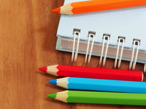 Colored pencils with blank sketch book on wooden background Stock Photo