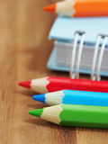 Colored pencils with blank sketch book on wooden background Stock Photos