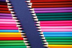 Colored pencils on blue background lying in opposite corners Royalty Free Stock Image