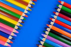Colored pencils  on blue background with reflection Royalty Free Stock Photos