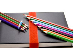 Colored pencils on book. With bowl royalty free stock image