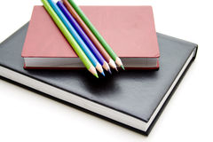Colored pencils on book Stock Photos