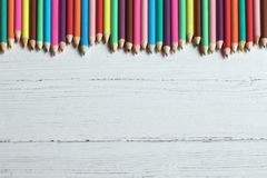 Colored pencils border on a wooden background, with copy space royalty free stock photos