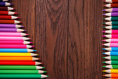 Colored pencils on brown background lying in opposite sides of wooden table stock images