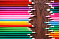 Colored pencils on brown wooden background lying in opposite each other. Table. Drawing and painting. School and education Royalty Free Stock Photos