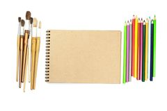 Colored pencils, brushes, notebook mock up for artwork with watercolor paints. Branding stationery mockup scene, blank objects for placing your design royalty free stock images