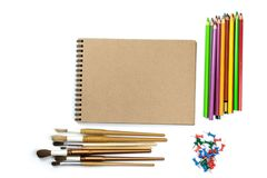 Colored pencils, brushes, notebook mock up for artwork with watercolor paints. Branding stationery mockup scene, blank objects for placing your design stock photography
