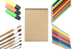 Colored pencils, brushes, notebook mock up for artwork with watercolor paints. Branding stationery mockup scene, blank objects for placing your design royalty free stock photo