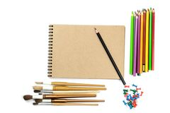 Colored pencils, brushes, notebook mock up for artwork with watercolor paints. Branding stationery mockup scene, blank objects for placing your design royalty free stock image