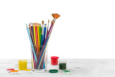Colored pencils and brushes to draw in glass and watercolor pain. Ts on light wooden background Stock Photography