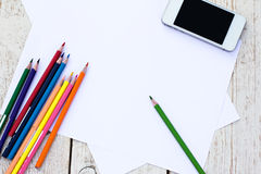 Colored pencils, cell phone and paper Royalty Free Stock Images