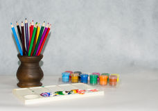 Colored pencils in a ceramic vase, a palette and paints Royalty Free Stock Photos