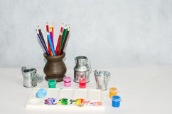 Colored pencils in a ceramic vase, a palette and paints Stock Photography