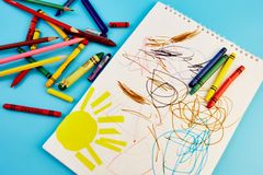 Colored pencils and children`s drawings. On a blue background royalty free stock photo