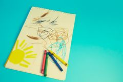 Colored pencils and children`s drawings. On a blue background royalty free stock photography