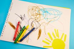 Colored pencils and children`s drawings. On a blue background royalty free stock image