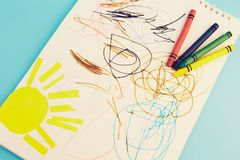 Colored pencils and children`s drawings. On a blue background stock images