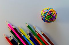Colored pencils on a clean sheet. ball of rubber bands stock image