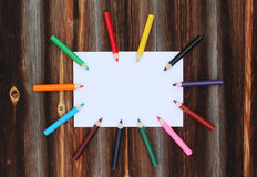 Colored pencils on a clean sheet of paper on old wooden background Royalty Free Stock Images