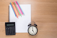 Colored pencils, clock and calculator on notebook Stock Photos