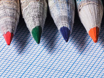 Colored pencils close-up on a background of graph paper Royalty Free Stock Images