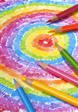Colored Pencils On Color Drawing. Color pencils lying on a brightly colored drawing Royalty Free Stock Photography