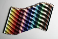 Colored pencils on colored papers arranged as a crossroads. Colored pencils on colored corners arranged as a crossroads with full colors Stock Photography