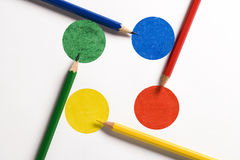 Colored pencils on colored disks arranged as a crossroads. Painted with pencils Royalty Free Stock Photo