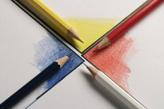 Colored pencils on colored papers arranged as a crossroads. Colored pencils on colored corners arranged as a crossroads with full colors Royalty Free Stock Images