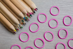 Colored pencils, colored rubber bands on wooden background Stock Image