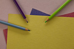 Colored pencils on colorful paper. Royalty Free Stock Photography