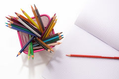 Colored pencils and copybook stock photo