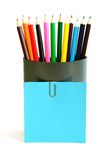 Colored pencils in cup with blue blank card Royalty Free Stock Images