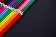 Colored pencils on dark background lying in opposite corners Stock Photography