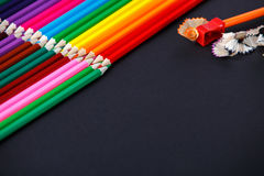 Colored pencils on dark background lying in opposite corners and one pencil with sharpener and shavings Stock Photography