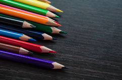Colored pencils on dark background. Set of colored pencils isolated on the wooden desk. Close up, right to left, space for text, top view Stock Photo
