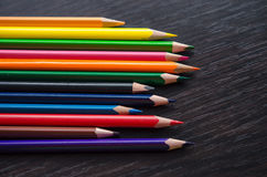 Colored pencils on dark background. Set of colored pencils isolated on the wooden desk. Close up, right to left, space for text, top view Stock Image