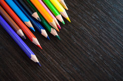 Colored pencils on dark background. Set of colored pencils isolated on the wooden desk. Close up, right to left, space for text, top view Stock Images
