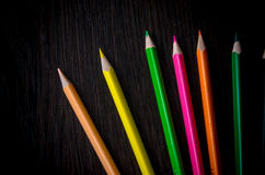 Colored pencils on dark background. Set of colored pencils isolated on the wooden desk. Close up, right to left, space for text, top view Stock Photos