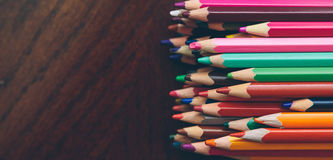 Colored pencils. On a dark wooden background Royalty Free Stock Image