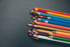 Colored pencils. On a dark wooden background Royalty Free Stock Photography
